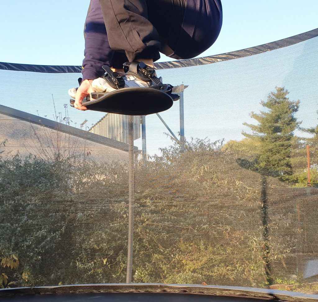 Snowboard Indy Grab oefenen met een Trampoline Board, zij aanzicht